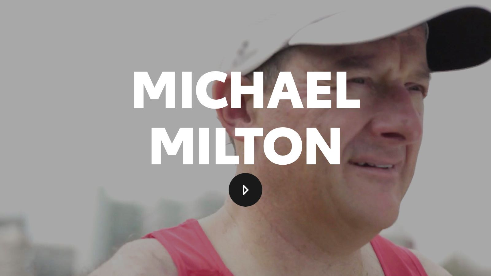 Michael Milton looks into the distance in a casual baseball hat and red tank top.