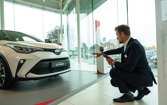 sales consultants shows Toyota C-HR to a customer through a video call