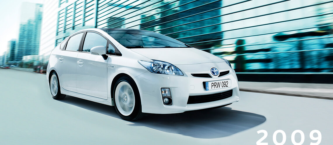 Toyota Prius, exterior White, front side view, driving shot, daytime city view.