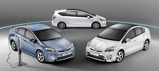 A few Prius vehicles parked in a circle next to an electric charger, grey background.