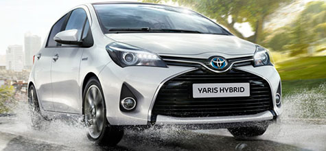 Toyota Yaris, exterior front side view, daytime city view, driving past a puddle, water splashes